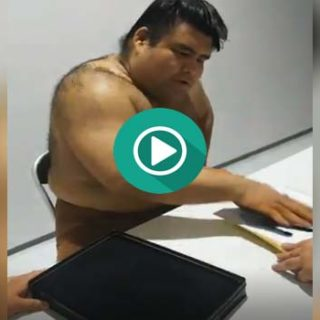 Un luchador de sumo firmando autógrafos con la mano.