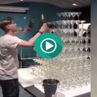 Divertido Fail creando una pirámide con copas de champan.
