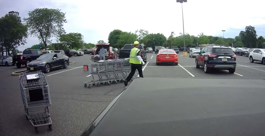 Empleado del supermercado intentando controlar los carritos de la compra 2